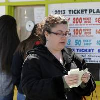 Photo - Shelley Myers walks from a ticket booth, counting her tickets on opening day at The Keansburg Amusement Park, Saturday, March 23, 2013, in Keansburg, N.J. Founded in 1904, the Keansburg Amusement Park, which Superstorm Sandy left under up to six feet of water, opens Saturday even though not all rides will be ready to operate and its popular Wildcat roller coaster is gone. (AP Photo/Mel Evans)