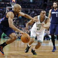Photo - Charlotte Bobcats' Gerald Henderson (9) drives past Boston Celtics' Avery Bradley (0) as the Bobcats' Josh McRoberts (11) looks on in the second quarter of an NBA basketball game in Boston, Friday, April 11, 2014. (AP Photo/Michael Dwyer)