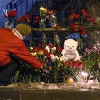 Photo - A women puts a flower outside a wreckage of a trolleybus in Volgograd, Russia, Tuesday, Dec. 31, 2013. Russian authorities ordered police to beef up security at train stations and other facilities across the country after a suicide bomber killed 14 people on a bus Monday in the southern city of Volgograd. It was the second deadly attack in two days on the city that lies just 400 miles (650 kilometers) from the site of the 2014 Winter Olympics. (AP Photo/Denis Tyrin)