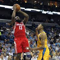 Photo - Houston Rockets guard James Harden (13) shoots over New Orleans Hornets forward Anthony Davis in the first half of an NBA basketball game in New Orleans, Friday, Jan. 25, 2013. (AP Photo/Gerald Herbert)