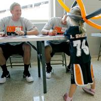 Photo - OSU quarterback Brandon Weeden (left) smiles at Megan Trolinger, age 5 of Inola, Oklahoma and her balloon cowgirl hat while Weeden and Clint Chelf (right) sign autographs during Oklahoma State's Fan Appreciation Day at Gallagher-Iba Arena in Stillwater, Oklahoma on Saturday, Aug. 6, 2011. Photo by John Clanton, The Oklahoman ORG XMIT: KOD