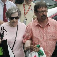Photo - Powerball winner Gloria C. Mackenzie, 84, left, leaves the lottery office escorted by her son, Scott Mackenzie, after claiming a single lump-sum payment of about $370.9 million before taxes on Wednesday, June 5, 2013, in Tallahassee, Fla. Officials say she is the largest sole lottery winner in U.S. history. She did not speak to reporters outside lottery headquarters, leaving in a silver Ford Focus with family members. (AP Photo/Steve Cannon)