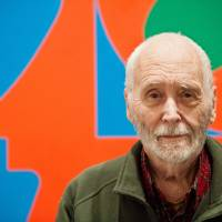 Photo - In this Sept. 24, 2013 photo, artist Robert Indiana, known world over for his LOVE image, is interviewed in front of that painting at New York's Whitney Museum of American Art. Surrounded by 95 works he created over the past five decades, Indiana, who turned 85 this month, calls the retrospective