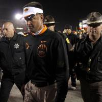 Photo - Oklahoma State coach Mike Gundy walks off the field after OSU's double-overtime loss in a college football game between the Oklahoma State University Cowboys (OSU) and the Iowa State University Cyclones (ISU) at Jack Trice Stadium in Ames, Iowa, Friday, Nov. 18, 2011. Photo by Bryan Terry, The Oklahoman