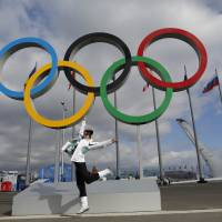 Photo - A woman jumps as she poses for a photo in front of the Olympic rings at Olympic Park ahead of the 2014 Winter Olympics, Sunday, Feb. 2, 2014, in Sochi, Russia.(AP Photo/Natacha Pisarenko)