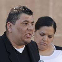Photo - Plaintiff Michael Duran, left, who received nearly $1 million in a sex abuse settlement with the Roman Catholic Archdiocese of Los Angeles, speaks during a news conference on Thursday, March 14, 2013 in Los Angeles. Duran was molested by ex-priest Michael Baker, who is now in jail after pleading guilty to a dozen sex charges. The U.S. church's challenges include recovering from the clergy sexual abuse scandal, which has resulted in the bankruptcies of prominent archdioceses and cost the Church in America an estimated $3 billion in legal settlements. Duran's wife, Margarita, looks on at right. (AP Photo/Damian Dovarganes)