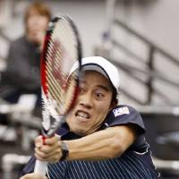 Photo - Kei Nishikori,of Japan, hits a return to Ivo Karlovic, of Croatia, in the singles final at the U.S. National Indoor Tennis Championships on Sunday, Feb. 16, 2014, in Memphis, Tenn. (AP Photo/Rogelio V. Solis)