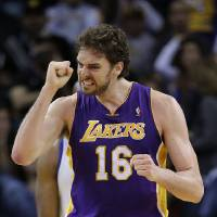 Photo - Los Angeles Lakers' Pau Gasol (16) celebrates after scoring against the Golden State Warriors during the second half of an NBA basketball game in Oakland, Calif., Saturday, Dec. 22, 2012. Los Angeles won in overtime 118-115. (AP Photo/Marcio Jose Sanchez)