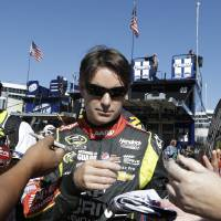 Photo - Driver Jeff Gordon signs autographs for fans while heading to the garage before practice for Sunday's NASCAR Sprint Cup series auto race at the Texas Motor Speedway in Fort Worth, Texas, Friday, Nov. 1, 2013.  (AP Photo/LM Otero)