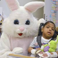 Photo - The Easter Bunny visits Khamar Norwood and other patients Wednesday at The Children's Center in  Bethany. PHOTOs provided BY JAMIE DAVIS OF THE CHILDREN'S CENTER
