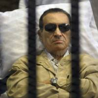 Photo - FILE - In this June 2, 2012 file photo, Egypt's ex-President Hosni Mubarak lays on a gurney inside a barred cage in the police academy courthouse in Cairo, Egypt. An Egyptian security official says ousted president Hosni Mubarak has been interrogated over gifts worth millions of Egyptian pounds (hundreds of thousands of US dollars) he allegedly received from the country's top newspaper as a show of loyalty while he was in power. Mubarak is serving a life sentence after being convicted for failing to stop killings of protesters during 2011 uprising. (AP Photo/File)