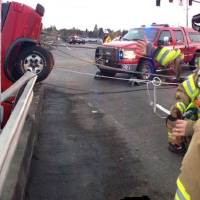 Photo -   This image provided by the Beaverton Police Department shows a red pickup truck dangling from the Denney Road overpass near highway 217 outside Beaverton, Oregon as emergency workers respond to the scene Saturday afternoon Nov. 24, 2012. The driver has been identified as Matthew Alan Hamilton 38 years old of Beaverton. He was taken to the hospital with unkown injuries after being plucked from the truck by firefighters. Hamilton has been arrested for DUI, driving while suspended for a previous misdemeanor DUI. (AP Photo/Beaverton Police Department)