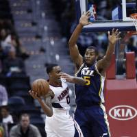 Photo - Atlanta Hawks point guard Jeff Teague (0) tries to pass as Utah Jazz power forward Derrick Favors (15) defends in the first half of an NBA basketball game on Friday, Jan. 11, 2013, in Atlanta. (AP Photo/John Bazemore)
