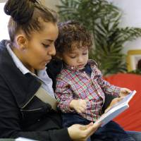Photo - Karla Rodriguez reads Friday to her son, Izack Perez, 1. She hopes to benefit from the planned opening of a Variety Care health clinic at Emerson High School. Photo by Doug Hoke, The Oklahoman