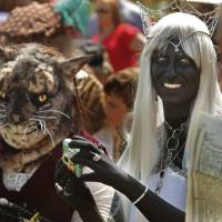 Photo - Stefany Belisle, dressed as a cat, and Cari Elliott, portraying a dark elf, wait for their category in a costume contest at last year's Medieval Fair in Norman.
