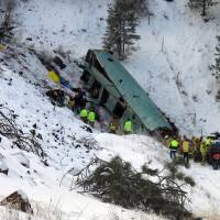 Photo - Emergency personnel respond to the scene of a multiple-fatality accident where a tour bus careened through a guardrail along an icy highway and several hundred feet down a steep embankment, authorities said, Sunday, Dec. 30, 2012 about 15 miles east of Pendleton, Ore. The charter bus carrying about 40 people lost control around 10:30 a.m. on the snow- and ice-covered lanes of Interstate 84, according to the Oregon State Police. (AP Photo/East Oregonian, Tim Trainor)