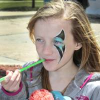 Photo - Cross Timbers Elementary School fifth-grader Mackenzie Westphalen eats a snow cone at the Downtown Edmond Arts Festival. Photo By David McDaniel, The Oklahoman  David McDaniel - The Oklahoman