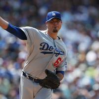 Photo - Los Angeles Dodgers starting pitcher Josh Beckett turns to make pickoff throw against the Colorado Rockies in the third inning of a baseball game in Denver on Sunday, July 6, 2014. (AP Photo/David Zalubowski)