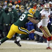 Photo - San Francisco 49ers quarterback Colin Kaepernick (7) runs against Green Bay Packers inside linebacker Brad Jones (59) during the first half of an NFL wild-card playoff football game, Sunday, Jan. 5, 2014, in Green Bay, Wis. (AP Photo/Mike Roemer)