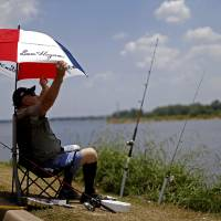 Photo - John Parson adjusts his umbrella as while fishing during his day off at Lake Hefner, Tuesday in Oklahoma City. Photo by Bryan Terry, The Oklahoman  BRYAN TERRY