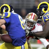 Photo - San Francisco 49ers outside linebacker Aldon Smith, center, sacks St. Louis Rams quarterback Sam Bradford, left, for a 6-yard loss while  Rams tackle Barry Richardson, right, tries to block Smith during the second quarter of an NFL football game Sunday, Dec. 2, 2012, in St. Louis. (AP Photo/Tom Gannam)