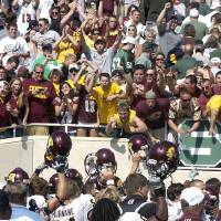 Photo - Central Michigan players hold up their helmets to fans after Central Michigan defeated Michigan State 29-27 in an NCAA college football game Saturday, Sept. 12, 2009, in East Lansing, Mich. (AP Photo/The Grand Rapids Press, Delbridge Langdon Jr.) ORG XMIT: MIGRA201