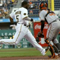 Photo - Pittsburgh Pirates' Josh Harrison (5) dashes home to score as Baltimore Orioles catcher Caleb Joseph waits for the relay throw in the first inning of the baseball game on Wednesday, May 21, 2014, in Pittsburgh . (AP Photo/Keith Srakocic)