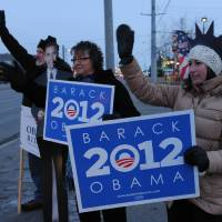 Photo -   John Hoffman, with a card board President Obama, Cindy Emery and Sarah Robinson wave signs in support of the President early on Election Day at the corner of the Seward Highway and Benson Boulevard in Anchorage on Tuesday, Nov. 6, 2012. (AP Photo/Anchorage Daily News, Bob Hallinen)