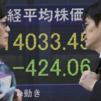 Photo - People walk by an electronic stock board of a securities firm in Tokyo, Wednesday, May 7, 2014. A dismal day on Wall Street spilled over into Asian trading Wednesday as jitters over the valuations of technology companies contributed to a sharp drop in Japan's benchmark. The Nikkei 225 stock index fell 2.3 percent to 14,120.25. Japanese markets were closed the previous two days for public holidays. (AP Photo/Eugene Hoshiko)