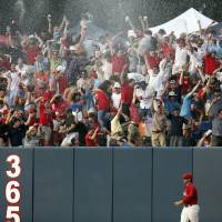 Photo - Jacksonville State outfielder Griff Gordon  takes a slow walk past the outfield wall as fans celebrate a sixth inning home run by Mississippi's Sikes Orvis during an NCAA college baseball regional tournament game in Oxford, Miss., Saturday, May 31, 2014. (AP Photo/Rogelio V. Solis)