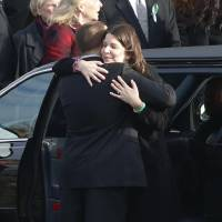 Photo - A man, left, hugs Krista Rekos following funeral services for her daughter, Jessica Rekos, at St. Rose of Lima Roman Catholic Church, Tuesday, Dec. 18, 2012, in Newtown, Conn. Jessica Rekos, 6, was killed when Adam Lanza walked into Sandy Hook Elementary School in Newtown, Conn., Dec. 14, and opened fire, killing 26 people, including 20 children, before killing himself. (AP Photo/Julio Cortez) ORG XMIT: CTJC124