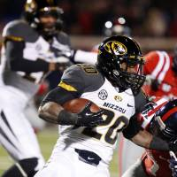 Photo -  Missouri running back Henry Josey (20) runs through Mississippi defenders for short yards in the second half of an NCAA college football game Saturday, Nov. 23, 2013, in Oxford, Miss. Missouri won 24-10. (AP Photo/Rogelio V. Solis)