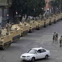 Photo - Egyptian army soldiers take their positions on top and next to their armored vehicles while guarding an entrance to Tahrir Square, in Cairo, Friday, Aug. 16, 2013. Egypt is bracing for more violence after the Muslim Brotherhood called for nationwide marches after Friday prayers and a