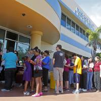 Photo -   Voters stand in line to pick up their absentee ballots in Doral, Fla., Sunday, Nov. 4, 2012. Christina White, deputy supervisor with Miami-Dade County, said the county also decided to accept absentee ballots for four hours on Sunday at its main office. (AP Photo/Alan Diaz)