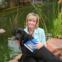 Photo - Pam Newby, executive director for Special Care Inc., sits with facility assistance dog Costa during a two-week June training program in Oceanside, Calif. PHOTO PROVIDED BY PAM NEWBY ORG XMIT: 0907250201222010