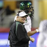 Photo -   Oregon head coach Chip Kelly, left, talks with quarterback Marcus Mariota late in the second half of an NCAA college football game against Washington State, Saturday, Sept. 29, 2012, in Seattle. Oregon beat Washington State 51-26. (AP Photo/Ted S. Warren)