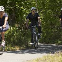 Photo - FILE - In this Aug. 15, 2014, file photo, first lady Michelle Obama, left, bikes rides with President Barack Obama and daughter Malia Obama on the Manuel F. Correllus State Forest bike path outside of West Tisbury, Mass., during the Obama family vacation on the island of Martha's Vineyard. Obama arrived on the Massachusetts island of Martha's Vineyard with one daughter, and the other daughter may be at his side when his two-week getaway ends later this month. In a first for Obama family summer vacations, neither teenager is spending the entire time with her father. (AP Photo/Jacquelyn Martin, File)
