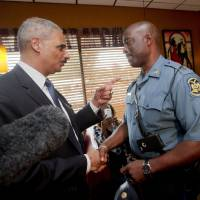 Photo - FILE - In this Aug. 20, 2014 file photo, Attorney General Eric Holder talks with Capt. Ron Johnson of the Missouri State Highway Patrol at Drake's Place Restaurant in Florrissant, Mo.  The Justice Department plans to open a wide-ranging investigation into the practices of the Ferguson, Missouri, Police Department following the shooting last month of an unarmed black 18-year-old by a white police officer in the St. Louis suburb, a person briefed on the matter said Wednesday, Sept. 3, 2014.  (AP Photo/Pablo Martinez Monsivais, File-Pool)