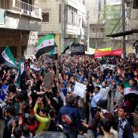 Photo - This citizen journalism image provided by Aleppo Media Center AMC which has been authenticated based on its contents and other AP reporting, shows anti Syrian regime protesters chanting slogans and waving the Syrian revolutionary flag during a demonstration, in Aleppo, Syria, Friday, April 19, 2013. Gunmen killed a government official in a Damascus restaurant, Syrian state media and activists reported Friday as regime troops and rebels fought fierce battles near the Lebanese border.(AP Photo/Aleppo Media Center, AMC)