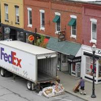 Photo -   FILE- In this Wednesday, May 23, 2012, file photo, a Federal Express truck makes a delivery in downtown Chagrin Falls, Ohio. FedEx Corp. says the global economy is worsening and it's cutting its forecast for the fiscal year ending in May. The world's second largest package delivery company says profit in the current quarter will be well below year ago results. (AP Photo/Amy Sancetta, File)