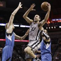 Photo - San Antonio Spurs' Manu Ginobili, center, of Argentina, shoots over Minnesota Timberwolves' Andrei Kirilenko, left, of Russia, during the first quarter of an NBA basketball game on Sunday, Jan. 13, 2013, in San Antonio. (AP Photo/Eric Gay)
