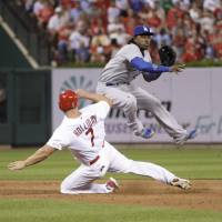 Photo - Los Angeles Dodgers shortstop Hanley Ramirez (13) leaps over a sliding St. Louis Cardinals' Matt Holliday (7) in the fourth inning of a baseball game, Sunday, July 20, 2014 in St. Louis.  (AP Photo/Tom Gannam)