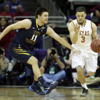 Photo - West Virginia's Nathan Adrian (11) pressures Texas' Javan Felix (3) during the first half of an NCAA college basketball game in the Big 12 men's tournament on Thursday, March 13, 2014, in Kansas City, Mo. (AP Photo/Charlie Riedel)