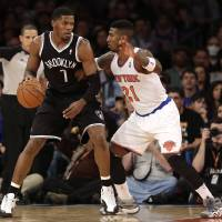 Photo - New York Knicks' Iman Shumpert, right, guards Brooklyn Nets' Joe Johnson during the first half of the NBA basketball game at Madison Square Garden, Monday, Jan. 20, 2014, in New York. (AP Photo/Seth Wenig)