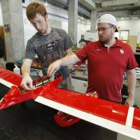 Photo - Derek Milligan, a senior from Oklahoma City, and Chase Knowles, a senior from Houston, work on the  University of Oklahoma's unmanned aerial vehicle in Norman.