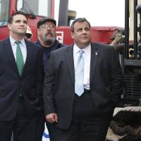 Photo - In this Wednesday, Jan. 9, 2013 photo, New Jersey Gov. Chris Christie, right, Belmar Mayor Matt Doherty, left, and others watch a pile-driver during a ceremony to kick off the construction of a new boardwalk in Belmar, N.J., to replace the walkway destroyed by Superstorm Sandy in October 2012. The stop was one of many on Gov. Christie's schedule following his State of the State message this week. With his popularity and visibility at record highs after Superstorm Sandy, Democrats are wondering if there is anyone left in the party to challenge him for re-election, beyond the one declared candidate who is not the first choice of the party establishment. (AP Photo/Mel Evans)