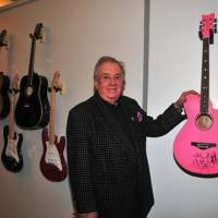 "Photo -  Music impresario Jim Halsey poses with Wanda Jackson's guitar at the January opening event for the exhibit ""Starmaker: Jim Halsey and the Legends of Country Music"" at the Gaylord-Pickens Oklahoma Heritage Museum. the In the background from left are other signed guitars from Halsey's collection, including guitars from Aerosmith, Kenny Rogers, BB King, Bob Dylan and Carlos Santana."