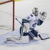 Photo - Dallas Stars center Tyler Seguin (91) scores a goal against Vancouver Canucks goalie Eddie Lack (31) during the first period of an NHL hockey game Thursday, March 6, 2014, in Dallas. (AP Photo/LM Otero)