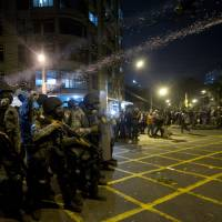 Photo - Military police fire tear gas at protestors during an anti-government protest near the Maracana stadium during the Confederations Cup final soccer match between Brazil and Spain, in Rio de Janeiro, Brazil, Sunday, June 30, 2013. Anti-government protesters are marching Sunday near the Maracana football stadium during a major international match, venting their anger about the billions of dollars the Brazilian government is spending on major sporting events rather than public services.(AP Photo/Silvia Izquierdo)