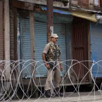 Photo - An Indian paramilitary soldier stands guard near a barbed wire set up as road blockade during restrictions in Srinagar, India, Friday, July 4, 2014. Shops, businesses and schools are shut in Indian-controlled Kashmir after separatist groups opposed to Indian rule announced a strike to protest a visit by the country's Prime Minister Narendra Modi. Modi is on his first official visit to the disputed Himalayan region and is expected to inaugurate a railway line and a power station, and also review security and development. (AP Photo/Dar Yasin)